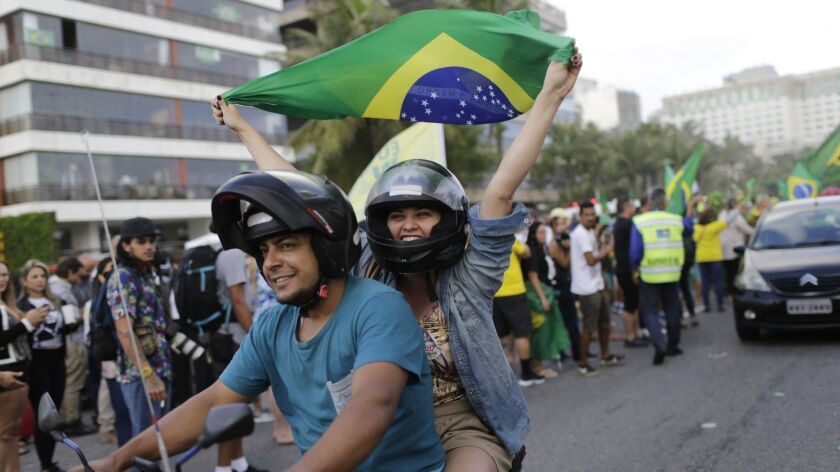A supporter of presidential front-runner Jair Bolsonaro rides on the back of a motorcycle waving a n