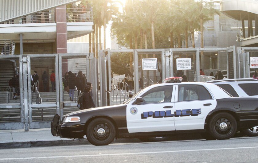 A police vehicle patrols by a school in Los Angeles on Dec. 16 after the L.A. Unified School District received an email threat that shut down schools for a day. In Long Beach on Thursday, the school district received a similar threat but is remaining open.