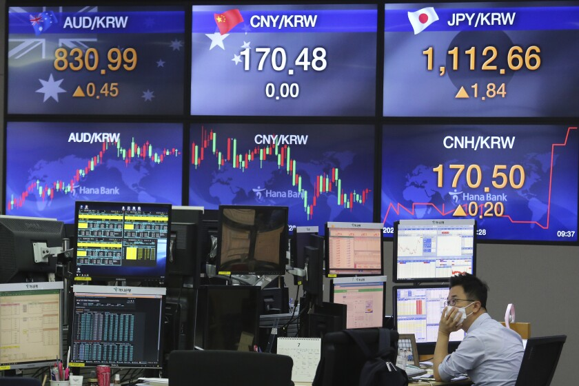 A currency trader watches monitors at the foreign exchange dealing room of the KEB Hana Bank headquarters in Seoul, South Korea, Wednesday, July 8, 2020. Asian shares were mostly lower Wednesday as uncertainty over the pandemic sapped the buying enthusiasm that has been driving prices higher. (AP Photo/Ahn Young-joon)