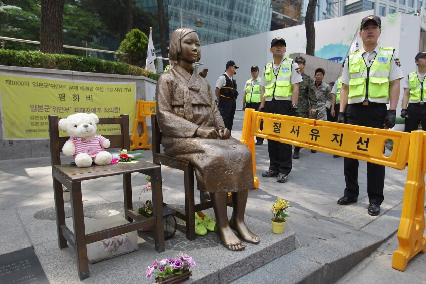 """South Korean police stand guard beside a """"comfort woman"""" statue during an anti-Japan rally in front of the Japanese embassy in Seoul."""