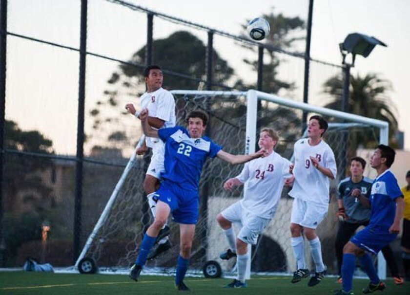 Chris Alleyne of The Bishop's School goes above La Jolla Country Day School's Alex Bigeriego (22) to head the ball away from the Knights' goal to defend a slim 2-1 lead in closing minutes of regulation Jan. 14. Also in view are Grant Brutten (24), Will Caples (9), and goalie Jakue Aguerre (rear right) of Bishop's, and Philip Lee (far right) of Country Day. Photo by Ed Piper