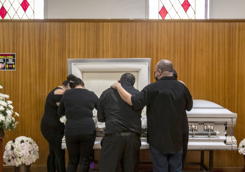Family members mourn a COVID-19 victim beside her casket.