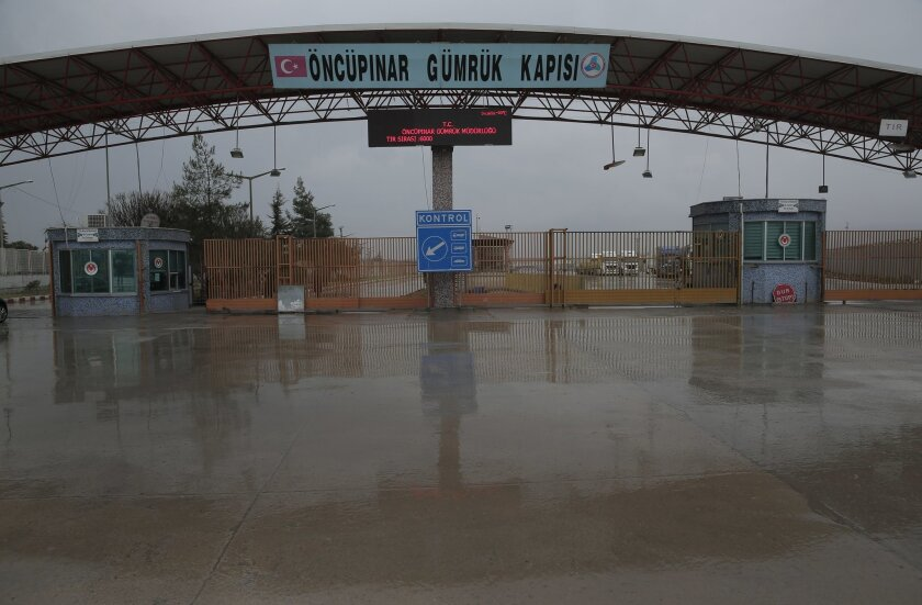 FILE - In this file photo dated Saturday, Feb. 6, 2016, the Turkish border crossing with Syria, is closed near to the town of Kilis, in southeastern Turkey, as some thousands of Syrian migrants are known to be moving toward the border, fleeing from fierce fighting inside Syria. Despite the wintry w