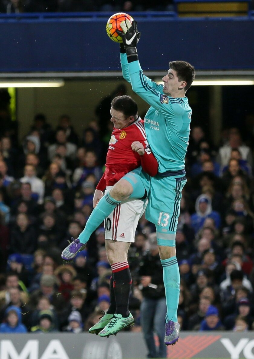 Chelsea's goalkeeper Thibaut Courtois, right, competes for the ball with Manchester United's captain Wayne Rooney during the English Premier League soccer match between Chelsea and Manchester United at Stamford Bridge stadium in London, Sunday, Feb. 7, 2016.  (AP Photo/Tim Ireland)