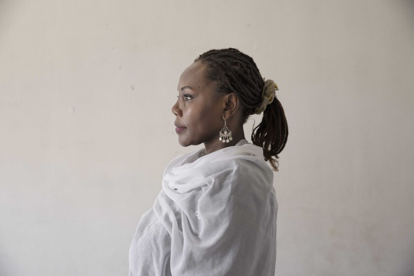 In this Sept. 4, 2019 photo, Sudanese activist Khalda Saber, poses for a photograph at her apartment, in Cairo, Egypt. Saber, a mother of two, was one of hundreds of thousands of Sudanese women who risked their lives leading protests that eventually pushed the military to overthrow al-Bashir in April. Under a joint military-civilian council in power now, they hope for more freedom and equality, and seek to overturn many of the restrictive Islamic laws from the previous era. (AP Photo/Nariman El-Mofty)
