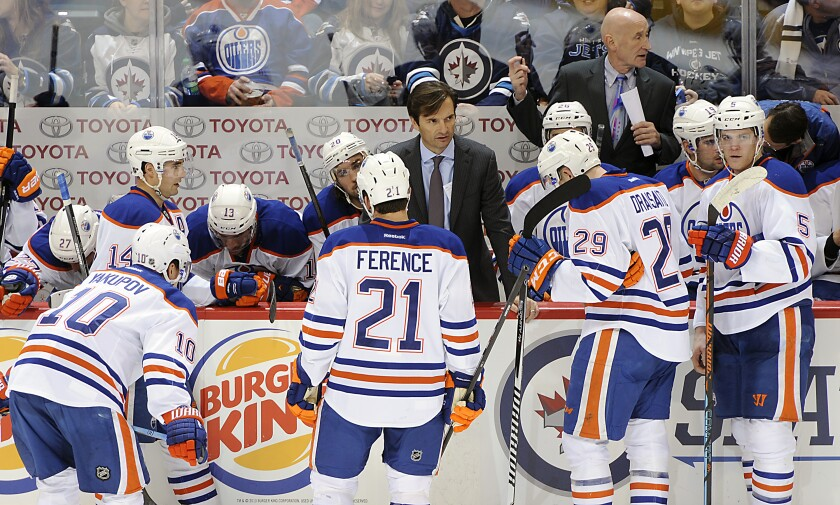 Edmonton Oilers coach Dallas Eakins speaks with his players during a timeout against the Winnipeg Jets in Dec. 2014.