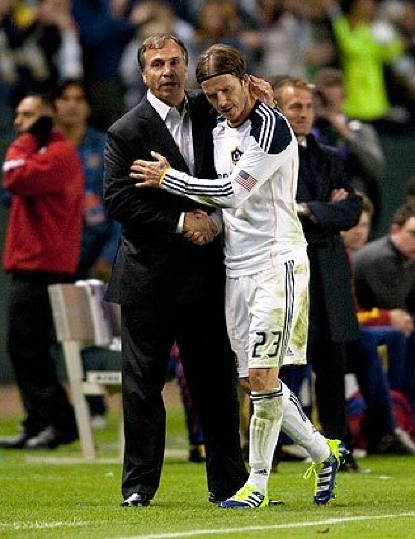 Galaxy Coach Bruce Arena embraces midfielder David Beckham after substituting for him in the final minutes of a 3-1 victory over Real Salt Lake in the MLS Western Conference championship game on Sunday at Home Depot Center.