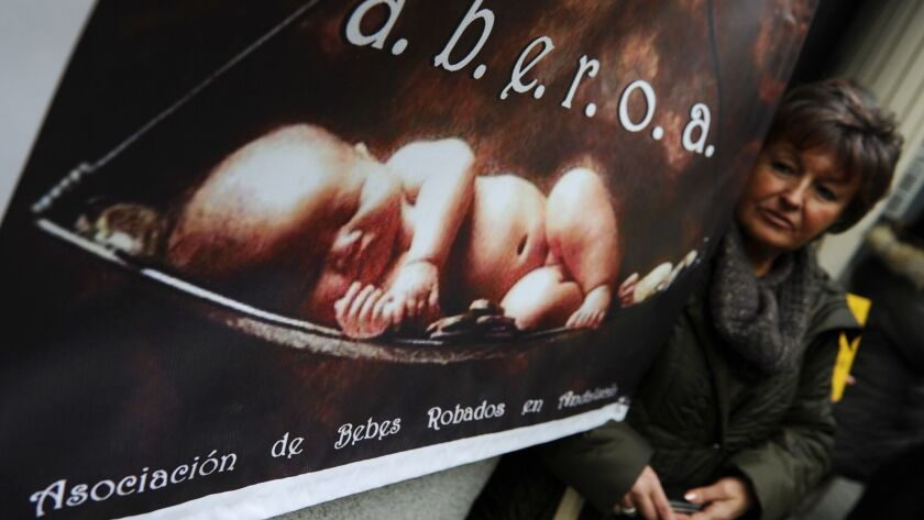 A woman poses next to a poster of the A.