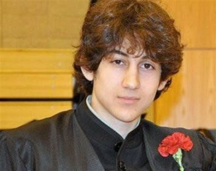 In this undated photo provided by Robin Young, Dzhokhar A. Tsarnaev, poses for a photo after graduating from Cambridge Rindge and Latin High School. Tsarnaev has been identified as the surviving suspect in the marathon bombings. Two suspects in the Boston Marathon bombing killed an MIT police offic