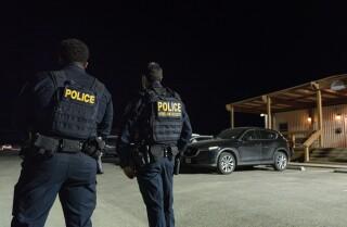Agents de el Departament de Seguretat Nacional esperen l'arribada de nens i adolescents immigrants procedents de la frontera sud dels Estats Units a un lloc de retenció temporal que va obrir el diumenge 14 de març de 2021, a sud de Midland, Texas. (Eli Hartman / Odessa American via AP)