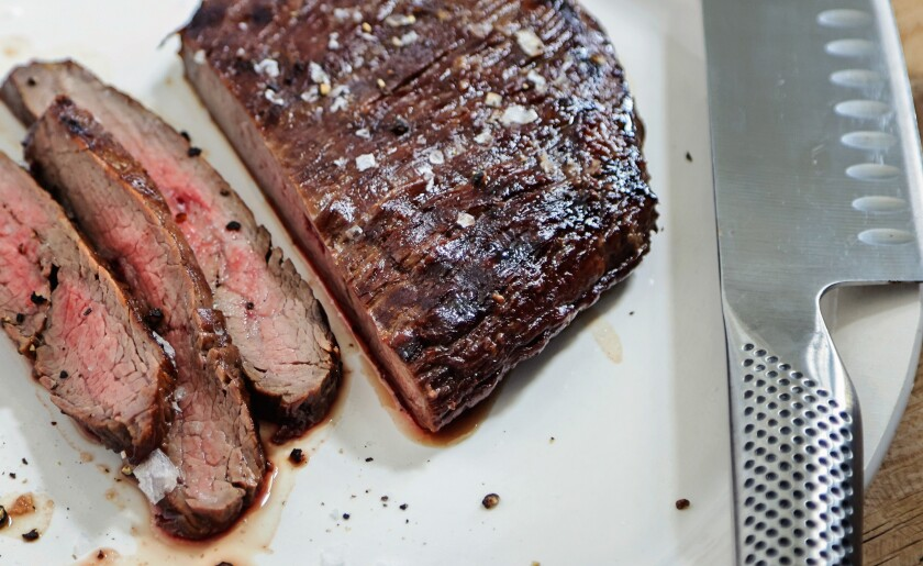 A marinated/grilled flank steak is sliced on a plate next to a knife.