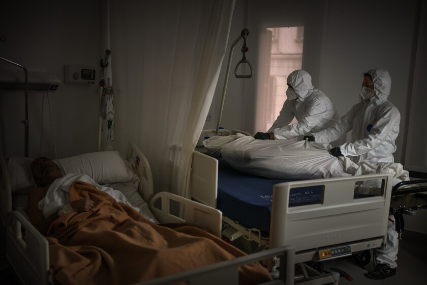 Wearing protective suits, funeral home workers remove the body of an elderly person who died of COVID-19 at a nursing home while another resident sleeps in his bed in Barcelona, Spain, Thursday, Nov. 5, 2020. In 2020, Spaniards have normalized things unimaginable only 12 months before. But 2020 will also go down as the year in which an unknown virus shook the foundations of the social contract and threw into question a system that failed to prevent so many deaths. (AP Photo/Emilio Morenatti)