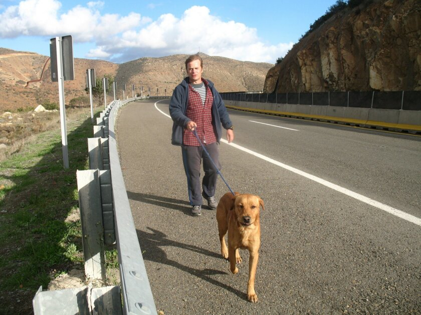 Tom Fremantle and his dog, Pancho, walk west toward Tijuana on the toll road from Tecate.