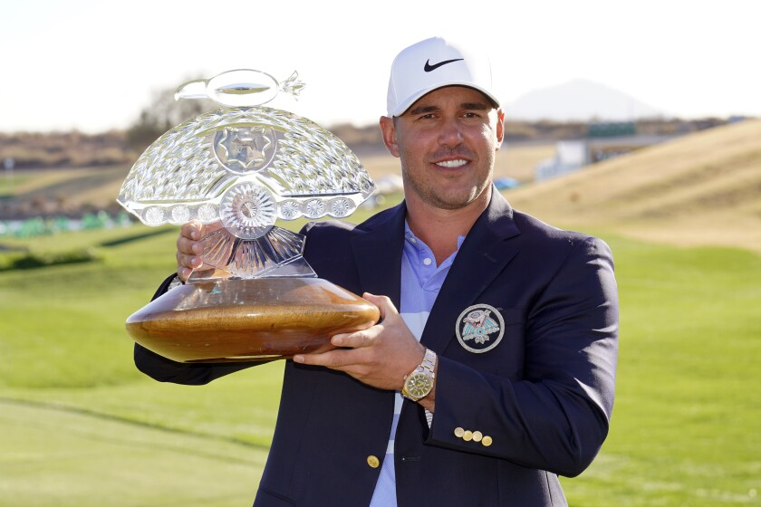 Brooks Koepka poses with the trophy after winning a PGA golf tournament on Sunday, Feb. 7, 2021.