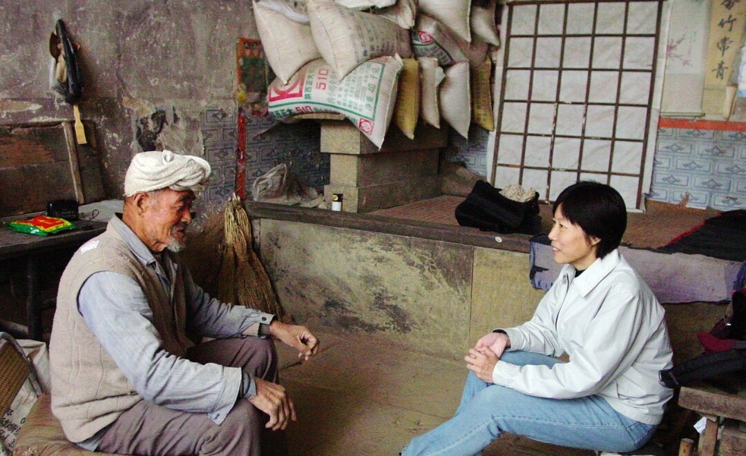Guo Yuhua interviews a villager in Ji village, Shaanxi province.