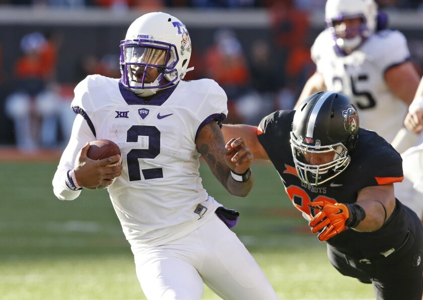 TCU quarterback Trevone Boykin (2) avoids a tackle by Oklahoma State defensive end Trace Clark, right, in the second quarter of an NCAA college football game in Stillwater, Okla., Saturday, Nov. 7, 2015. (AP Photo/Sue Ogrocki)