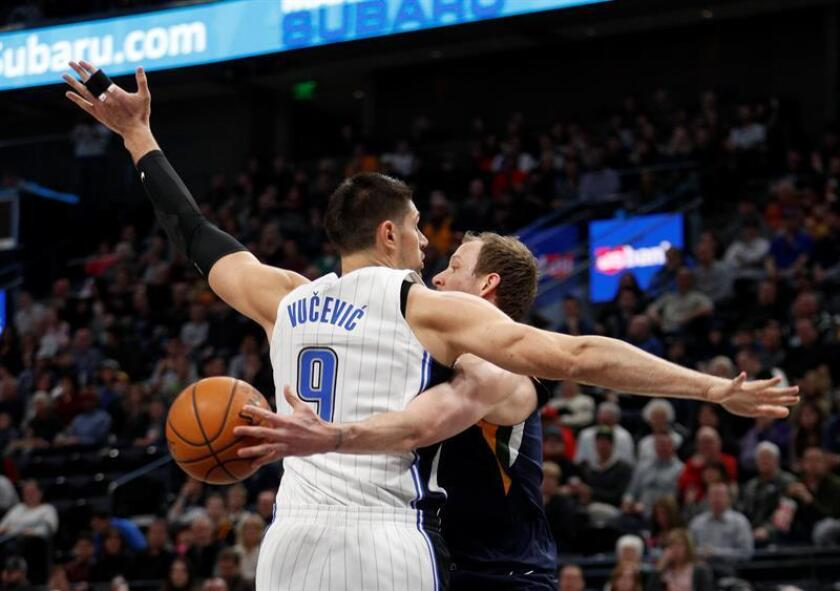 El alero de Utah Jazz Joe Ingles (d) pasa la pelota alrededor del pívot Nikola Vucevic (i) de Orlando Magic durante un juego de la NBA, en la Energy Solutions Arena de Salt Lake City, Utah (EE.UU.). EFE