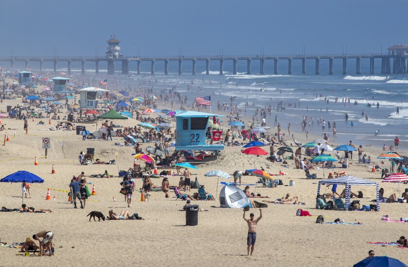 Thousands of beachgoers enjoy a warm, sunny day in Huntington Beach amid California's stay-at-home restrictions.