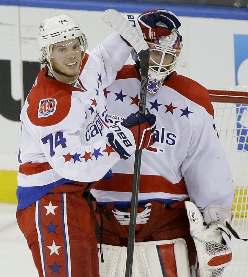 Washington Capitals defenseman John Carlson (74) congratulates goalie Braden Holtby (70) after the Capitals defeated the New York Rangers 2-1 in Game 1 of the second round of the NHL Stanley Cup hockey playoffs Thursday, April 30, 2015, in New York. (AP Photo/Frank Franklin II)