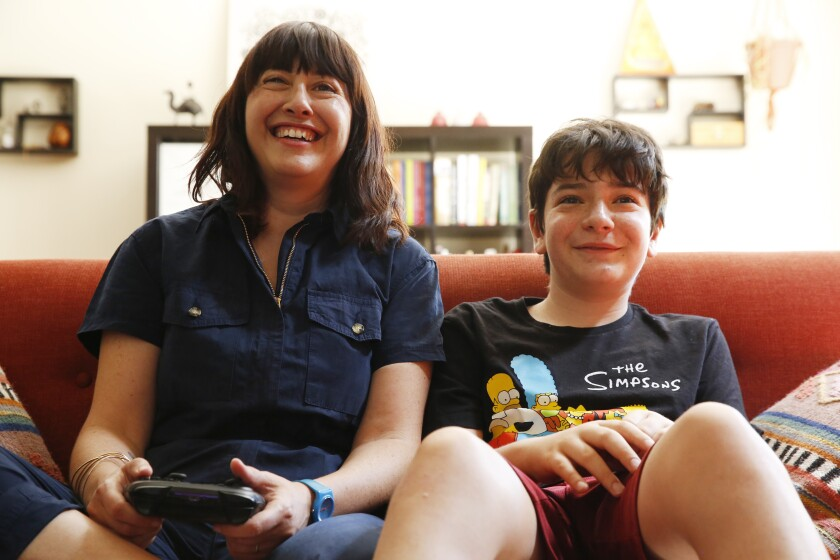 A woman holds a game console controller as she sits next to a boy on a couch.