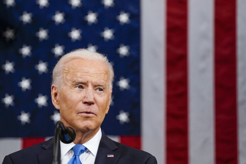 President Biden appears before an American flag.