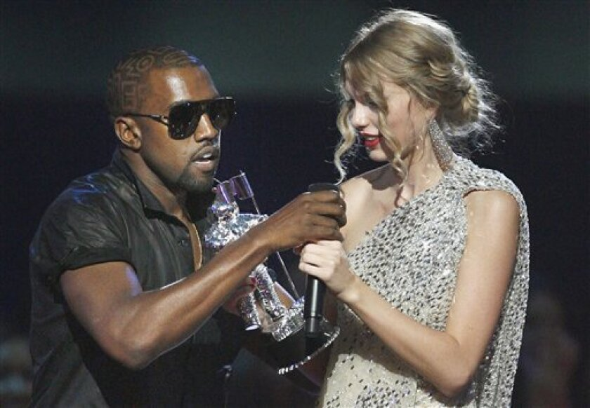 """FILE - In this Sept. 13, 2009 file photo, singer Kanye West takes the microphone from singer Taylor Swift as she accepts the """"Best Female Video"""" award during the MTV Video Music Awards in New York. West is still feeling the pain over his trophy grab from Taylor Swift last year, and he's expressing his pain all over Twitter. West has unleashed a torrent of emotions on his official Twitter on Saturday, Sept. 4, 2010, acknowledging he was wrong for taking an award from the country sweetheart at the MTV Video Music Awards. But he says he """"bled hard."""" He says he had to cancel his tour with Lady Gaga and even lost employees. (AP Photo/Jason DeCrow, File)"""