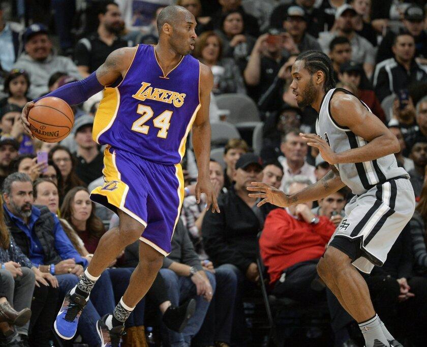 Los Angeles Lakers guard Kobe Bryant (24) attempts to evade San Antonio Spurs forward Kawhi Leonard during the second half of an NBA basketball game, Saturday, Feb. 6, 2016, in San Antonio. San Antonio won 106-102. (AP Photo/Darren Abate)