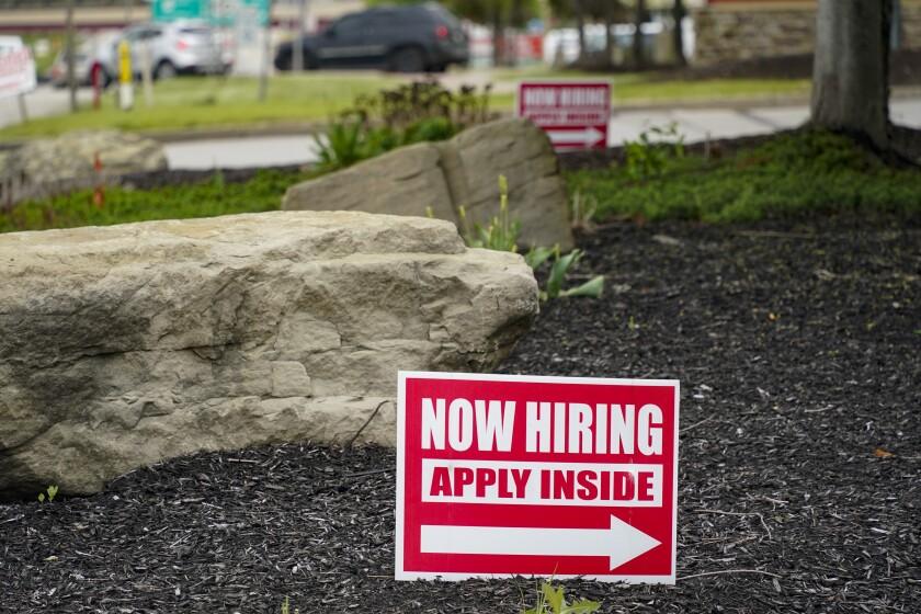 "A sign with an arrow says, ""Now hiring: Apply inside."""