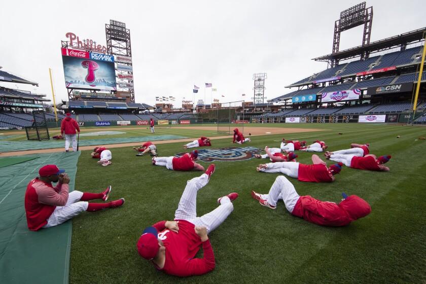 ARCHIVO - En esta fotografía del 7 de abril de 2017, jugadores de los Filis de Filadelfia calientan previo al juego del equipo contra los Nacionales de Washington, en Filadelfia. (AP Foto/Matt Rourke, Archivo)