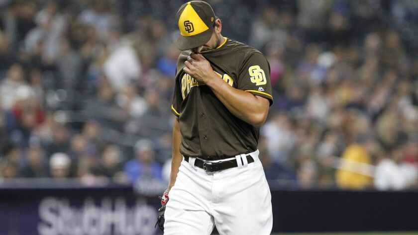 The Padres' Brad Hand walks back to the dugout after the Milwaukee Brewers scored five runs in the ninth inning at Petco Park in San Diego on Thursday.