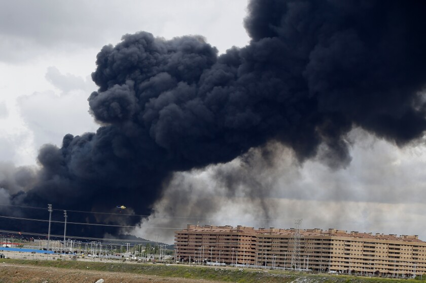 Black smoke from a massive tire fire rises from behind housing blocks in Sesena, Spain, on May 13.