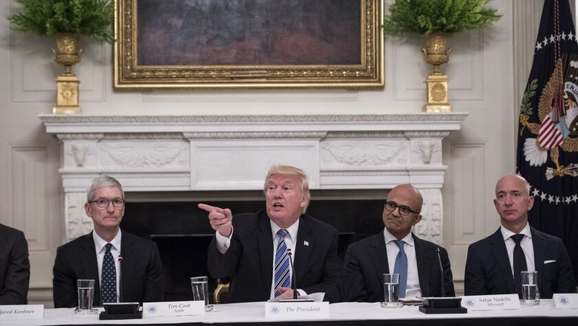 From left: Apple CEO Tim Cook, President Donald Trump, Microsoft CEO Satya Nadella and Amazon CEO Jeff Bezos, who owns The Washington Post, participate in an American Technology Council roundtable at the White House on June 19, 2017.