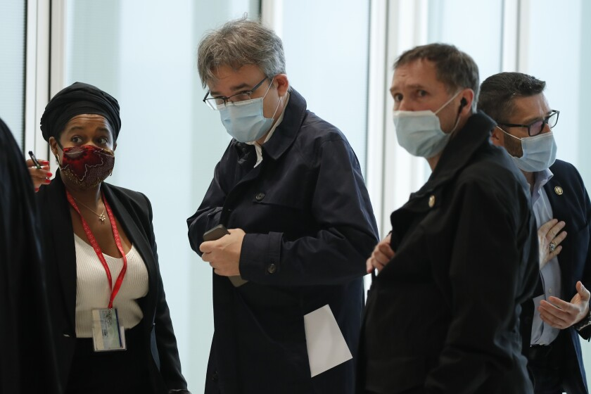 Satirical newspaper Charlie Hebdo's chief editor, Laurent Sourisseau, known as Riss, stands with others at courtroom.