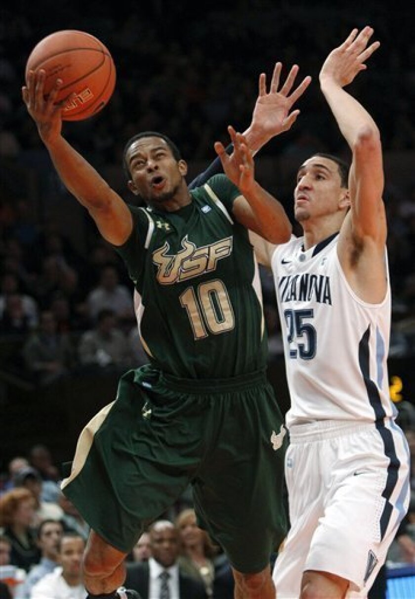 South Florida's Anthony Crater (10) drives past Villanova's Maurice Sutton (25) during the first half of an NCAA college basketball game at the Big East Championship, Tuesday, March 8, 2011, in New York. (AP Photo/Frank Franklin II)