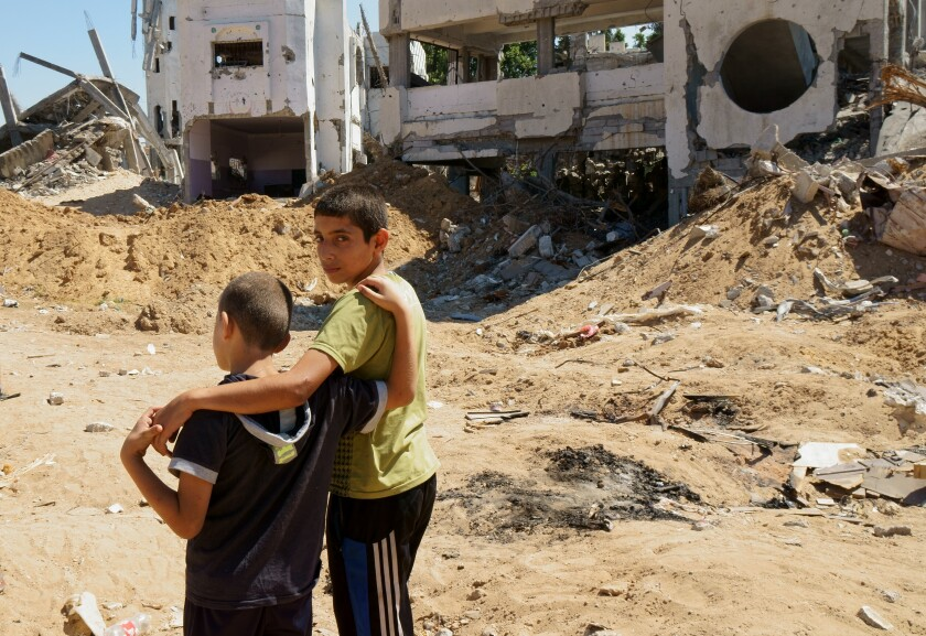 Two brothers from the Gaza City neighborhood of Shuja'iyya stand in front of their house.