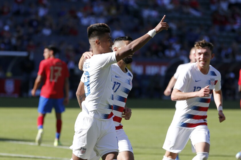 Ulysses Llanez, front left, reacts after making a penalty kick in the 50th minute to life the U.S. to a 1-0 exhibition win over Costa Rica on Feb. 1, 2020.