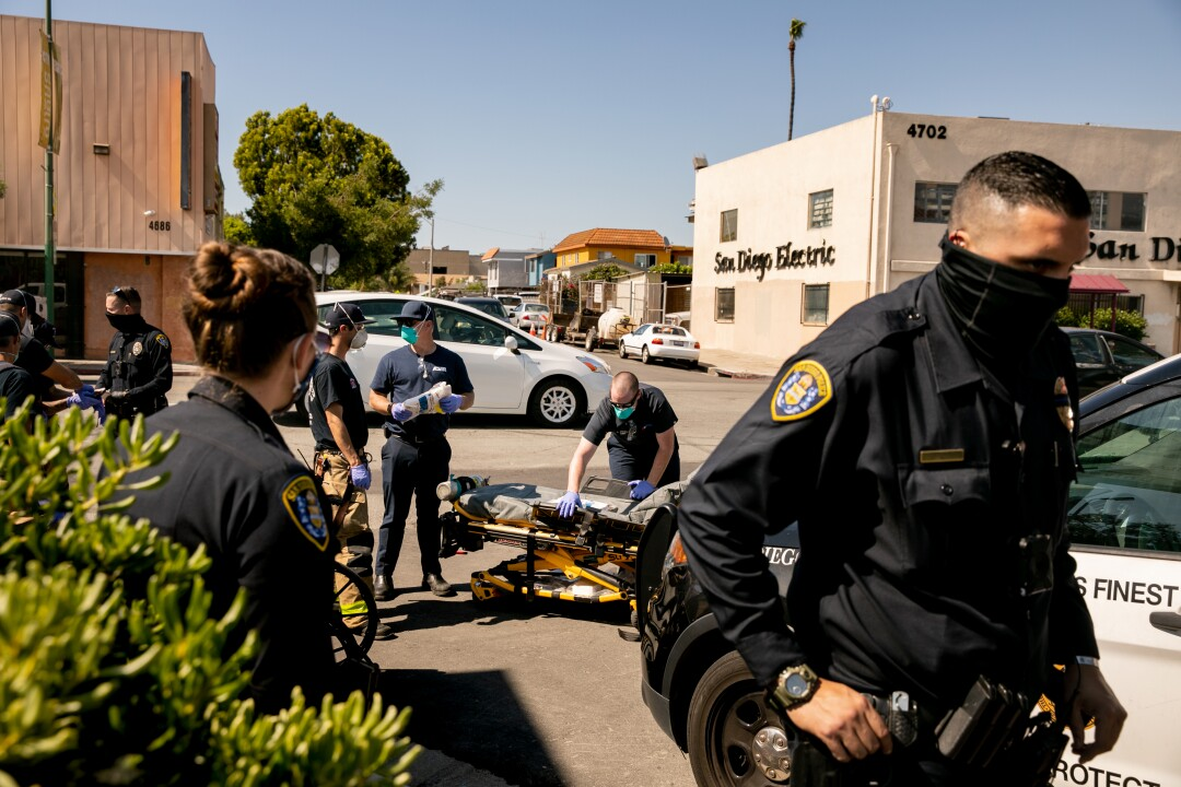 A handful of San Diego police officers and firefighters help a woman in distress.