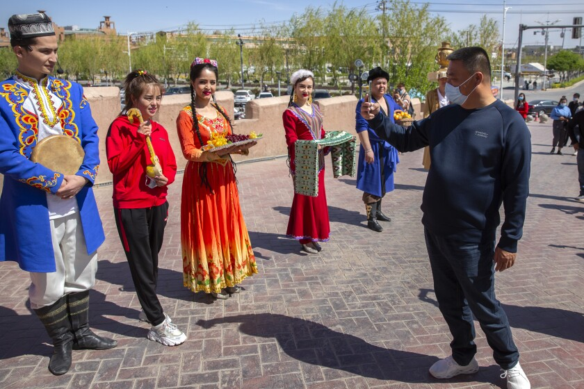 A tourist snaps pictures of Uyghur performers at the front gate of the remodeled city center of Kashgar in China's far west Xinjiang region, during the welcome ceremony of a state tour for foreign media on April 19, 2021. Four years after Beijing's brutal crackdown on largely Muslim minorities native to Xinjiang, Chinese authorities are dialing back the region's high-tech police state and stepping up tourism. But even as a sense of normality returns, fear remains, hidden but pervasive. (AP Photo/Mark Schiefelbein)