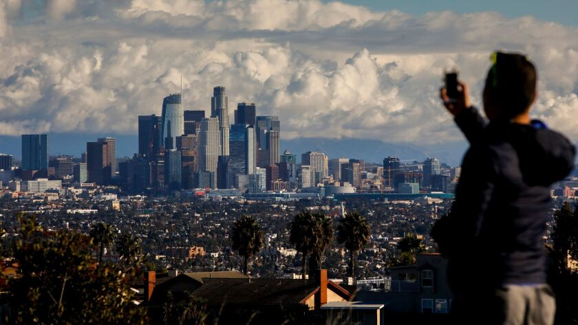 After dropping a friend at LAX airport, Mike Che, from West Hollywood, stopped at Kenneth Hahn State Recreation Area to take in the skyline of downtown Los Angeles, CA, following a winter storm, Christmas Eve morning.