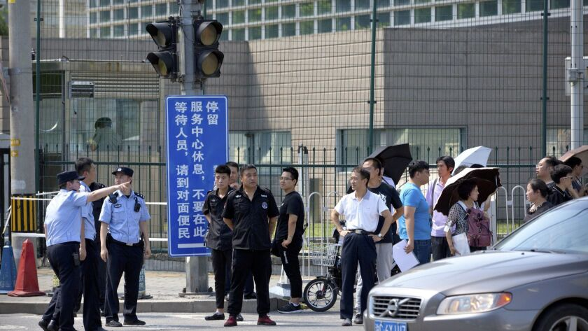 Chinese security personnel stand outside the U.S. Embassy, in the background, after a reported blast