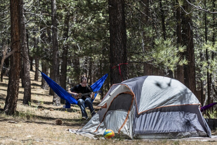 Camping with his family at Heart Bar Campground, Alex Ainsworth,15, plucks a guitar while lounging in a hammock.