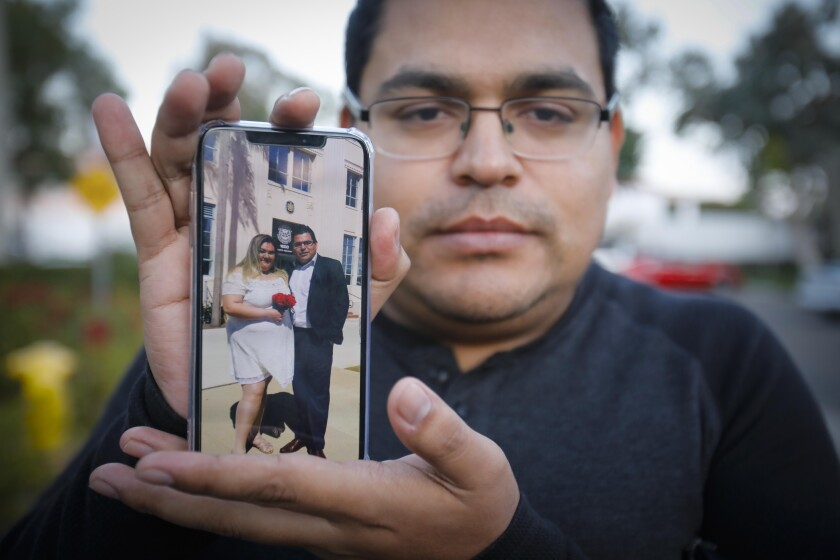 Ramón Mendoza, the husband of Maribel Ibañez, 28, who was killed when a gunman opened fire Wednesday night in the Church's Chicken in Otay Mesa, holds a cellphone photo showing their wedding day, on March 12th of this year.