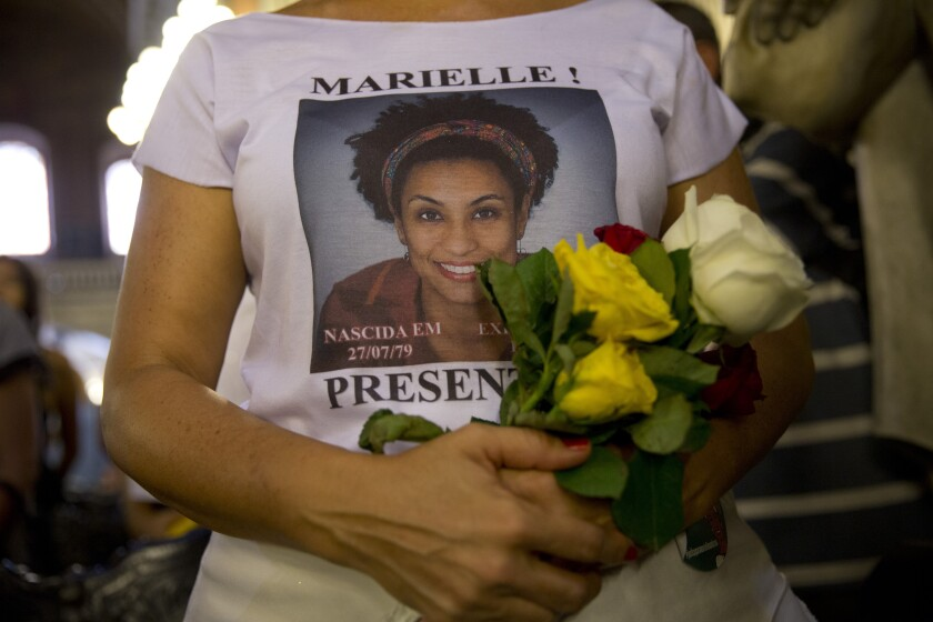 FILE - In this March 14, 2019 file photo, a woman wears a T-shirt designed with an image of slain councilwoman Marielle Franco during a memorial Mass to mark the one-year anniversary of her death, at the Candelaria Catholic Church in Rio de Janeiro, Brazil. Outgoing Brazilian Attorney General Raquel Dodge requested on Tuesday, Sept. 17, that five people be charged with obstructing justice in the case of councilwoman Franco. (AP Photo/Silvia Izquierdo, File)