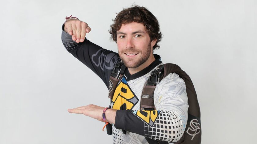 Portrait of skydiver Jesse Weyher with his parachute. He's using his hands to simulate his descent to earth while skydiving.