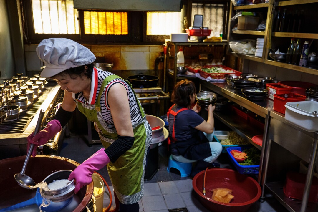 An Ji-shu, left, prepares rice to boil on the stove at Woosung Gisa Sikdang, in Seoul.