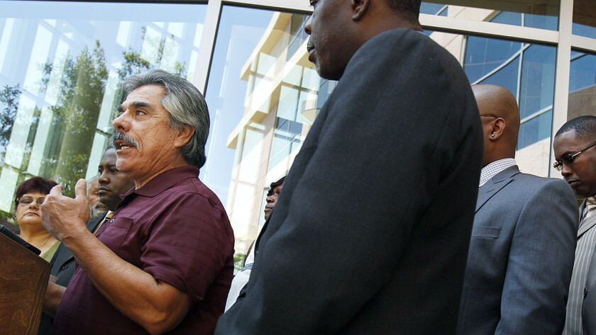 Javier Flores of the League of United Latin American Citizens, left, speaks in Lancaster during a news conference in 2013 in response to the Justice Department's allegations involving the L.A. County Sheriff's Department.