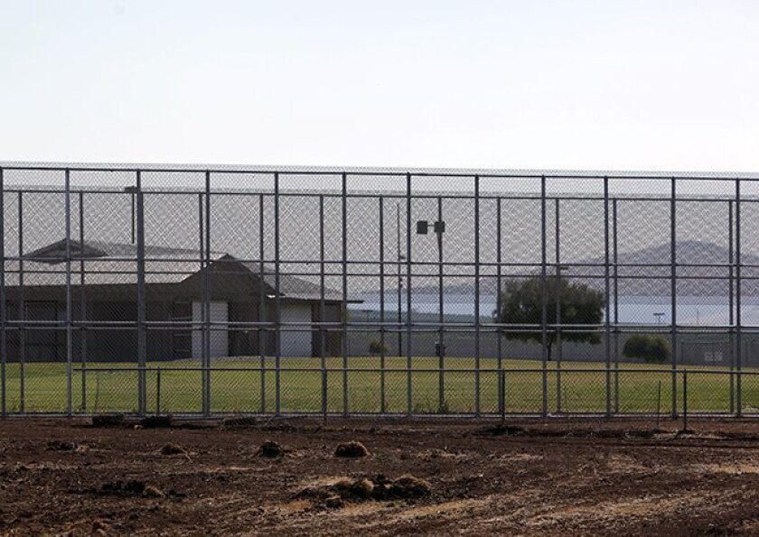 """A double fence encircles the """"secure treatment"""" section of the Porterville Developmental Center. California's courts have ruled the roughly 200 patients housed here unfit to stand trial and some a danger to themselves and others. CREDIT: Michael Fagans / The Center for Investigative Reporting"""