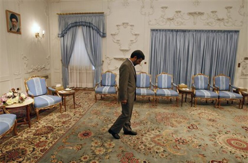 In front of a picture of Iranian supreme leader Ayatollah Ali Khamenei, President Mahmoud Ahmadinejad, waits to receive Omani Foreign Minister Yousuf bin Alawi bin Abdullah, unseen, for a meeting at the presidency, in Tehran, Iran, Saturday, July 11, 2009. (AP Photo/Vahid Salemi)