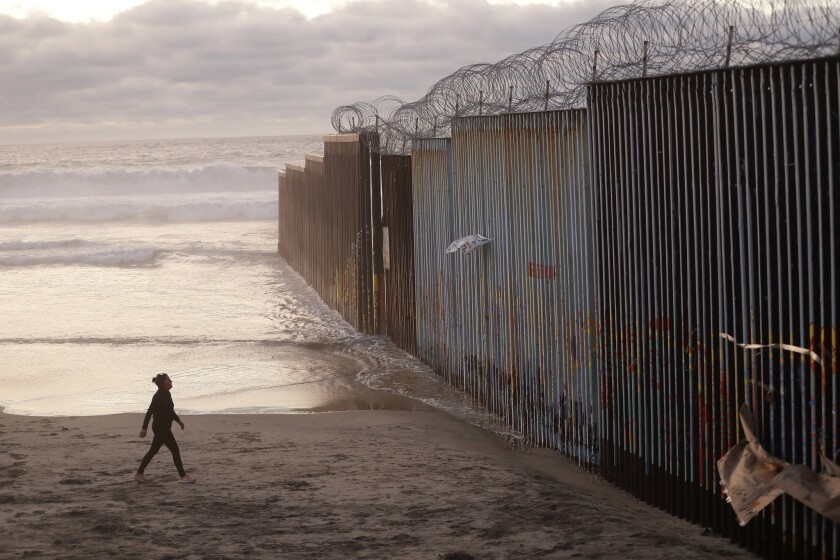A woman walks north on the beach in Tijuana, Mexico, on Jan. 9, 2019, up to the border fence with the United States.