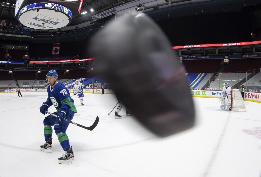 Vancouver Canucks' Tanner Pearson (70) waits for the puck to drop down after it was shot around the glass during the second period of an NHL hockey game against the Toronto Maple Leafs in Vancouver, British Columbia, on Saturday, March 6, 2021. (Darryl Dyck/The Canadian Press via AP)